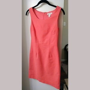 Coral color sheath style dress.